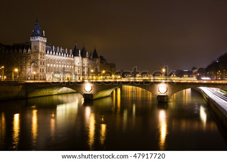 La Conciergerie and Pont au Change, over the Seine river at night - Paris, France