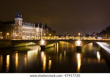 La Conciergerie and Pont au Change, over the Seine river at night - Paris, France - stock photo