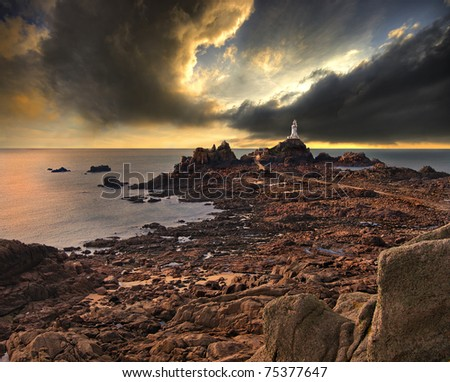 La Corbiere lighthouse on the island of Jersey, England, UK, with a dramatic sky in the background