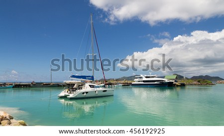 La Digue - 9 November 2014: The yacht and passenger ferry are in port and beautiful reflection in seawater November 9, 2014, La Digue, Seychelles