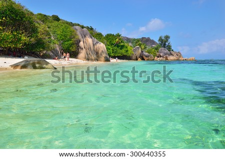 LA DIGUE, SEYCHELLES - JULY 2, 2011: Unidentified tourists have a rest on the beautiful sandy beach ource D'Argent - the most famous beach at the islands - stock photo