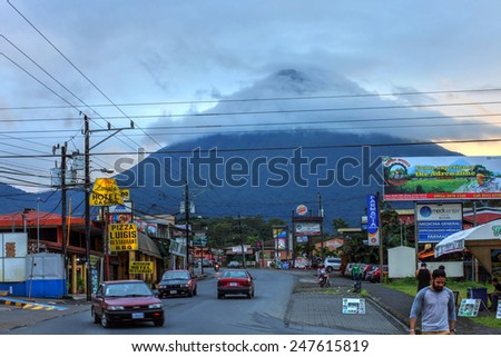 LA FORTUNA, COSTA RICA - JANUARY 19: Volcan Arenal looming over the touristic town of La Fortuna, Costa Rica at sunset time on January 19, 2015.  - stock photo