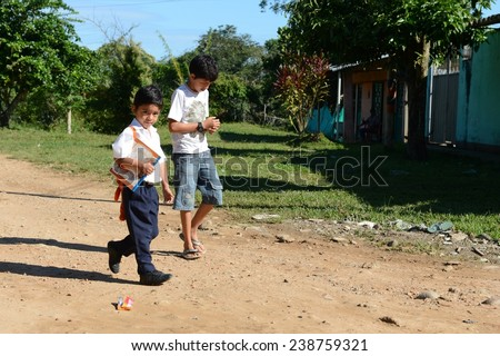 LA MACARENA, COLOMBIA - NOVEMBER 6, 2012: The town of La Macarena in the department of Meta, best known for its main natural attraction -  river Cano Cristales. Unidentified boys on street.