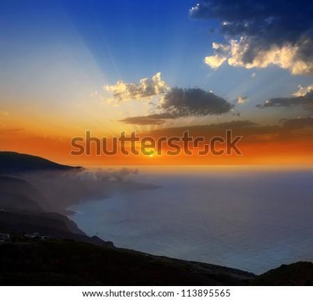 La Palma muntains sunset with orange sun in canary islands - stock photo