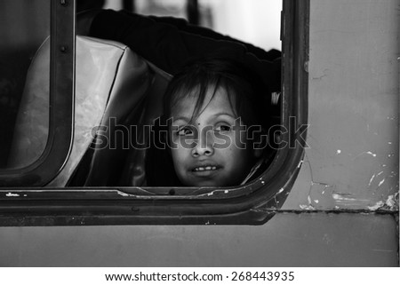 LA PAZ, BOLIVIA March 23, 2015: A young child looking out of a bus window - stock photo