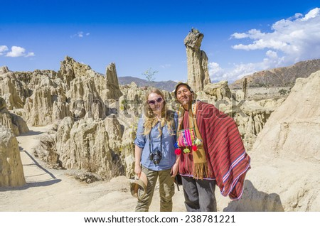 LA PAZ, BOLIVIA, MAY 9, 2014: Local man in traditional attire poses with young blond tourist in Moon Valley - stock photo