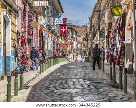 LA PAZ, BOLIVIA - NOV 4, 2015: Popular tourist and shopping streets of La Paz. The road is covered with old cobble stones.