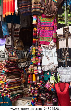 LA PAZ, BOLIVIA - NOVEMBER 10, 2014: Colorful sweaters, bags and scarves hanging outside a handicraft and souvenir shop on Linares street in the city center on November 10, 2014 in La Paz, Bolivia.  - stock photo