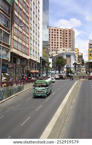 LA PAZ, BOLIVIA - NOVEMBER 28, 2014: Old Dodge bus driving on Villazon Avenue, statue of Mariscal Sucre on Plaza del Estudiante (Student's Square) in the back on November 28, 2014 in La Paz, Bolivia - stock photo
