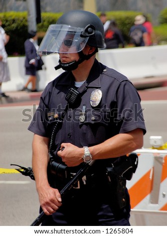 LA Police in riot gear watches over demonstrators at LA illegal emigrant rally. May 1st 2006 - stock photo