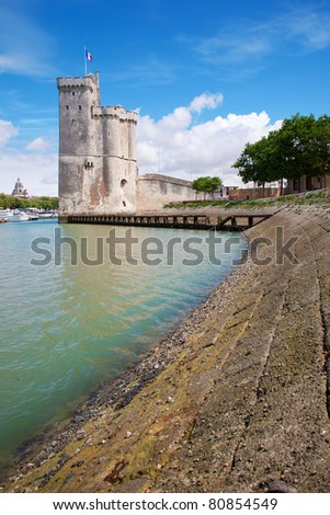 La Rochelle old harbor entrance, with a medieval tower waving the french flag in Charente-Maritime, France