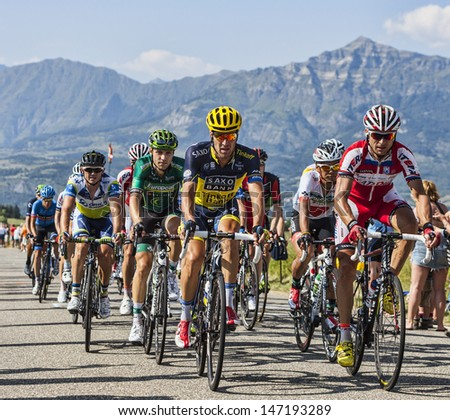 LA ROCHETTE, FRANCE- JUL 16: The peloton pedaling on a plain road after the ascension to Col de Manse in The Alps during the stage 16 of 100 edition of Le Tour de France on July 16 2013 in La Rochette - stock photo