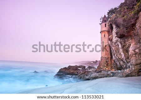 La Tour (the Tower) in Laguna Beach, California during a very early morning tide.  Very slow shutter speed used to capture the water motion and pink sky.