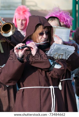 LAAB IM WALDE, AUSTRIA - MARCH 2011: Musician in the monks dress play flute at the annual carnival procession held on Mar 5, 2011 in Laab im Walde, Austria.