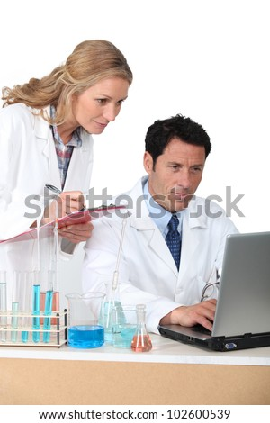 lab assistants on computer - stock photo