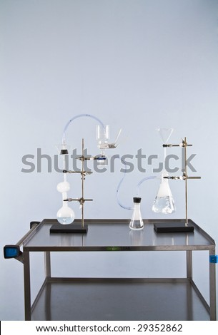 Lab glassware bubbles as test tubes and beakers fill with smoke and chemicals. - stock photo