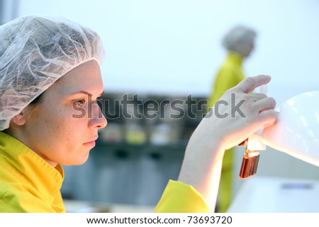 Lab technician inspecting the quality of glass ampules at a pharmaceutical factory. - stock photo