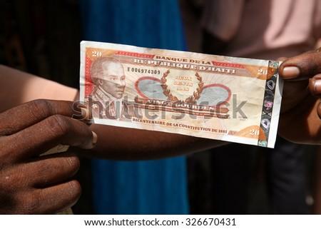 LABADEE, HAITI - SEPTEMBER 27, 2015: An unidentifiable Haiti resident displays Haitian Money to show their currency. Labadee, Haiti  - stock photo