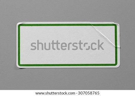 Label Adhesive Close Up on Grey Background with Real Shadow. Top View of Adhesive Paper Tag with Green Border. Stickers with Copy Space for Text or Image - stock photo