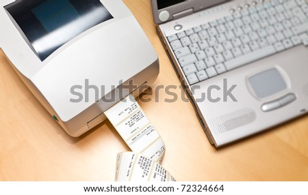Label and barcode printer next to a notebook