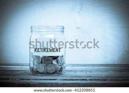 Label on a glass jar with the inscription - retirement. Glass jar with coins. Financial concept on wooden background - stock photo