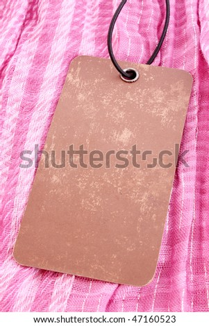 Label on pink textile background - stock photo