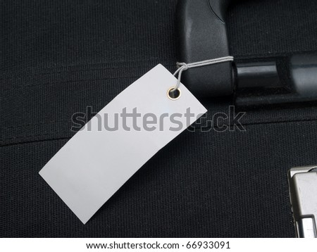 label tied to the handle of a suitcase - stock photo