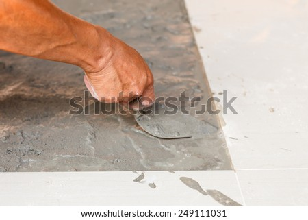 Labor installing tile floor for new house building - stock photo
