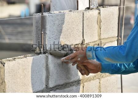 Labor using cement mortar masonry concrete block walls - stock photo