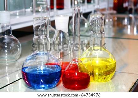 laboratory beakers with the coloured liquid - stock photo