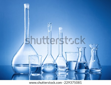 Laboratory equipment, bottles, flasks on blue background - stock photo