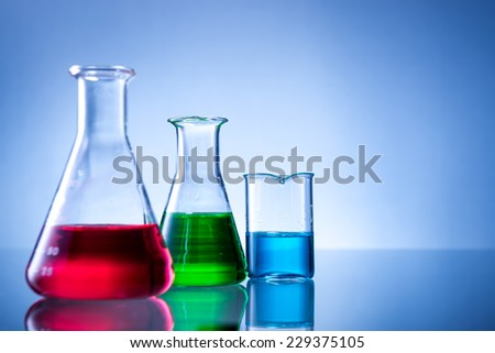 Laboratory equipment, bottles, flasks with color liquid  on blue background