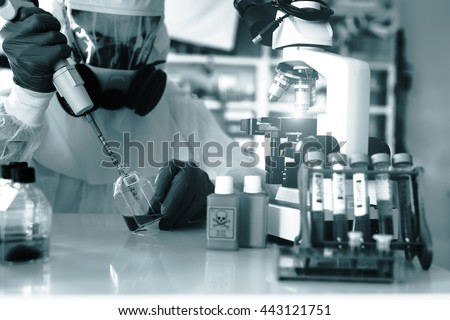 Laboratory examination of Ebola. Scientist takes blood pipette and microscope studies in biological samples.. Science concept. Blue colored image - stock photo