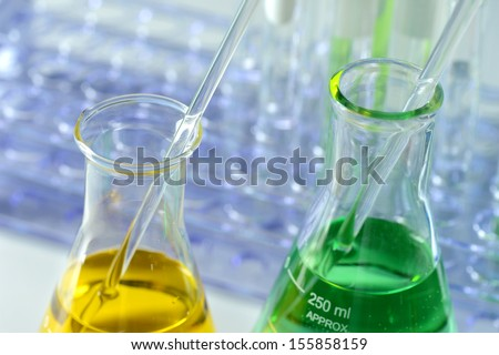 Laboratory flasks with colored liquids and glassware in background - stock photo