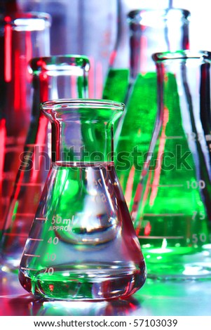 Laboratory glass conical Erlenmeyer flask filled with clear liquid and assorted glassware for an experiment in a science research lab