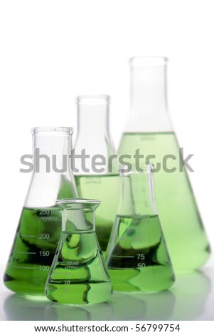 Laboratory glass conical Erlenmeyer flasks filled with green liquid for an experiment in a science research lab