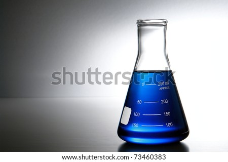 Laboratory glass Erlenmeyer conical flask filled with blue chemical liquid for a chemistry experiment in a science research lab - stock photo