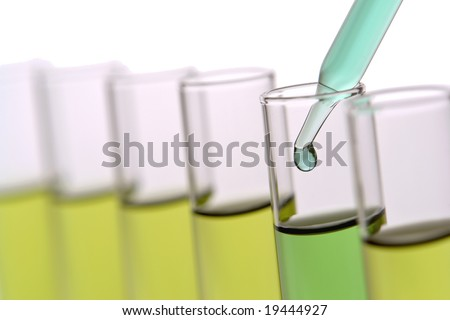 Laboratory glass pipette with drop of green liquid inside test tubes filled with yellow chemical solution for an experiment in a science research lab