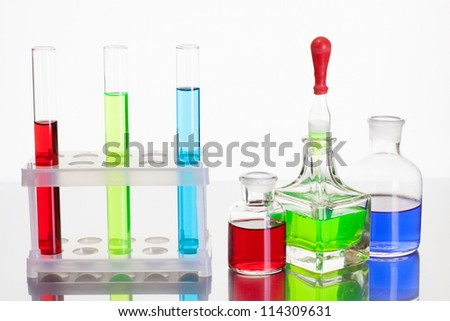 Laboratory glass test tubes with color liquid on white background - stock photo