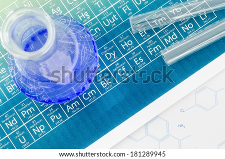 Laboratory glassware and periodic table of elements. - stock photo