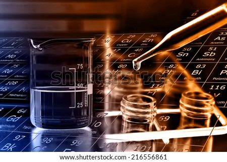 Laboratory glassware, beaker and test tubes in rack  - stock photo
