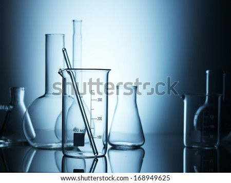 Laboratory glassware on color background - stock photo