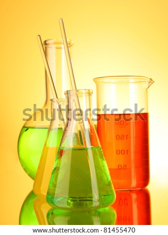 Laboratory glassware on yellow background - stock photo