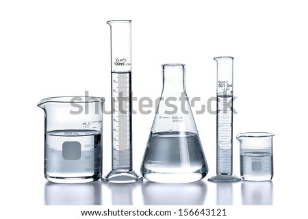 Laboratory glassware over reflective surface with white background - stock photo