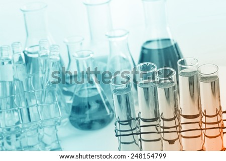 Laboratory glassware, test tubes and flasks with clear solution.