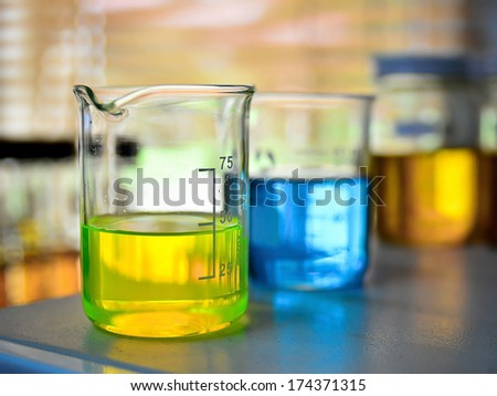 Laboratory glassware with blue and yellow liquid - stock photo