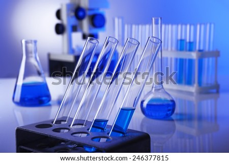 Laboratory glassware with blue liquid on bright background - stock photo