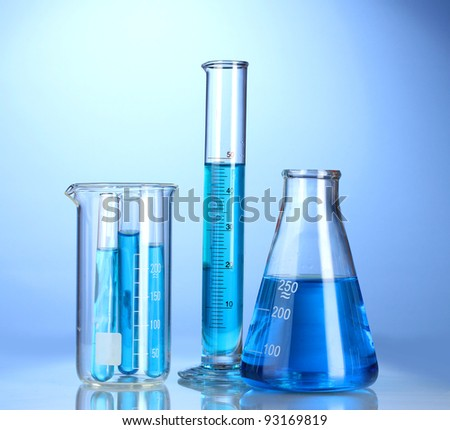 Laboratory glassware with blue liquid with reflection on blue background - stock photo