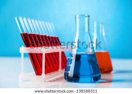 Laboratory glassware with chemistry probe against blue background - stock photo