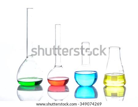 Laboratory glassware with colored liquids over reflective table over white - stock photo
